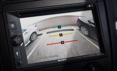Rear camera image of space behind car, shown on screen of AV centre