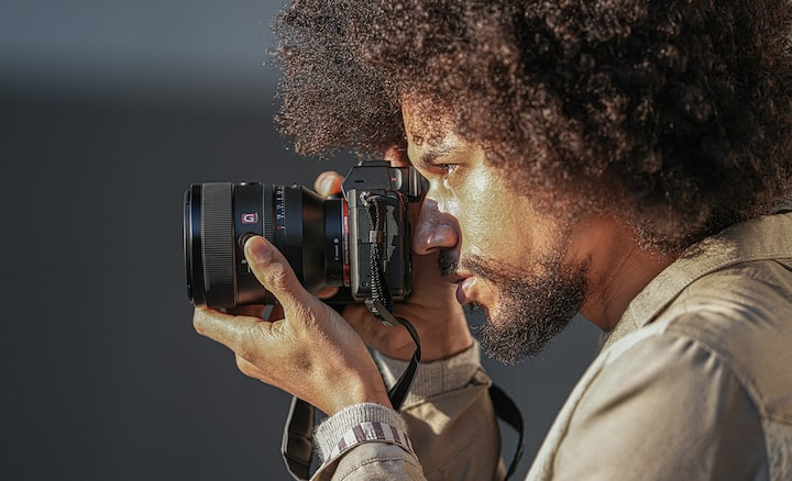 Image of a person holding a camera with the FE 50mm F1.2 GM lens attached