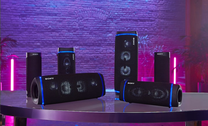SRS-XB43 on table alongside multiple Bluetooth compatible models with party lights